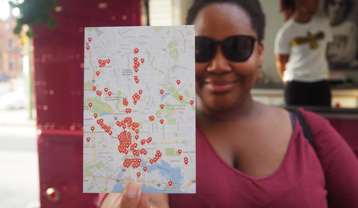 Woman holds a postcard showing a map of all the stories collected in Baltimore, Maryland?