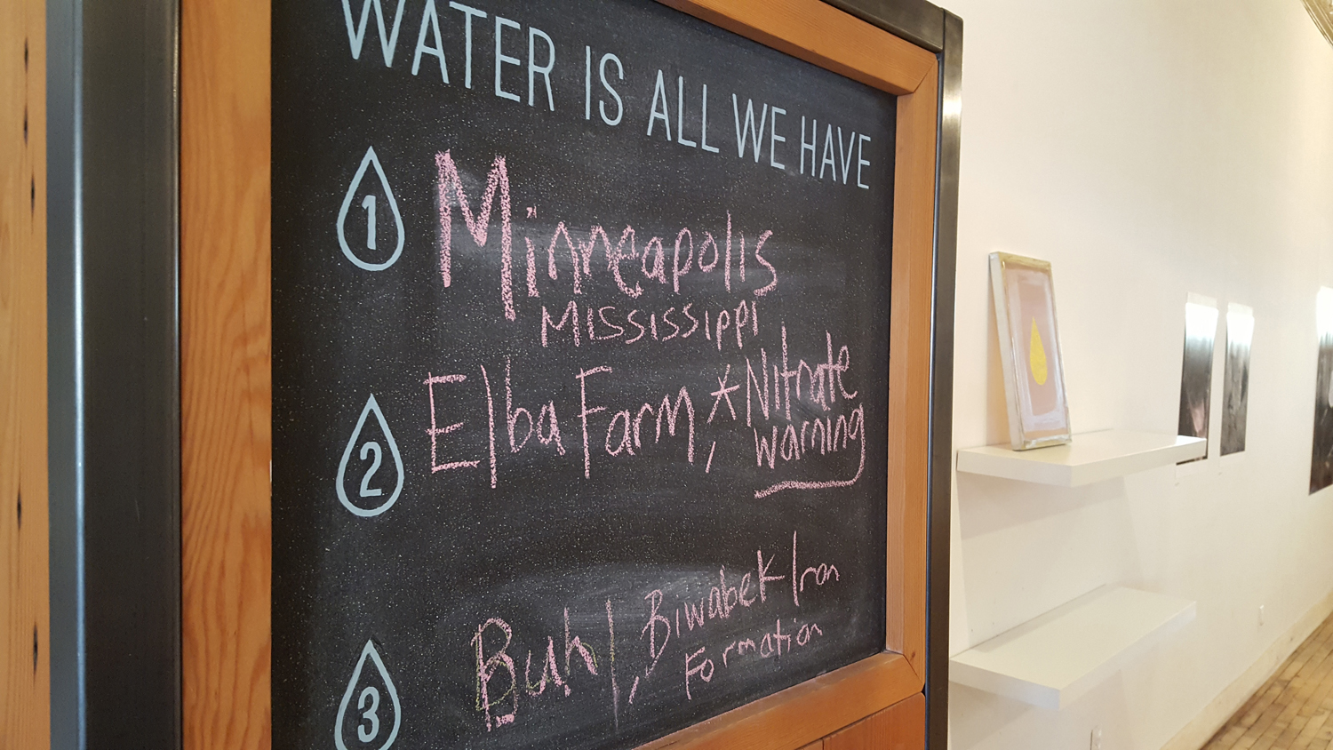 A chalk board shows notes about water-related issues. Inside the Water Bar in Minneapolis, Minnesota, visitors talk about how water issues affect their lives.