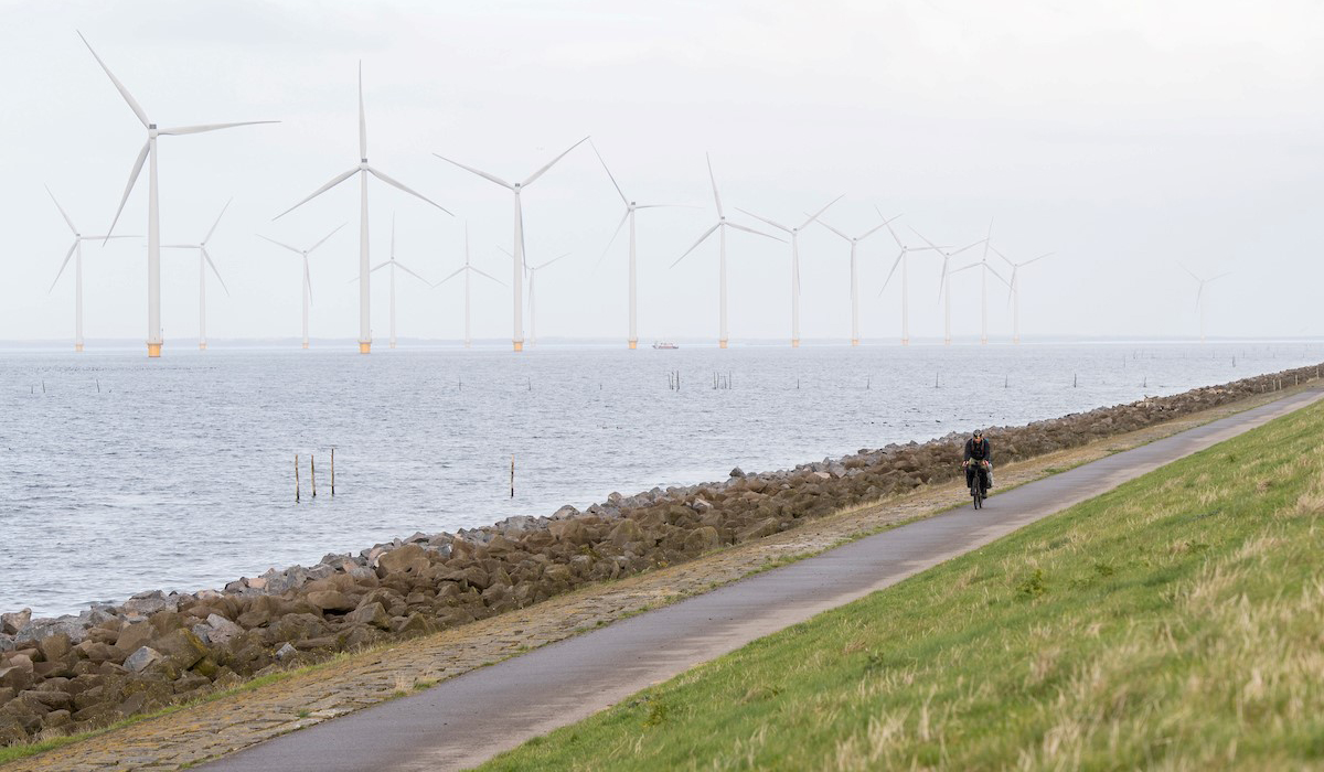 Ben Weaver rides his bike in front of a lake with windmills.