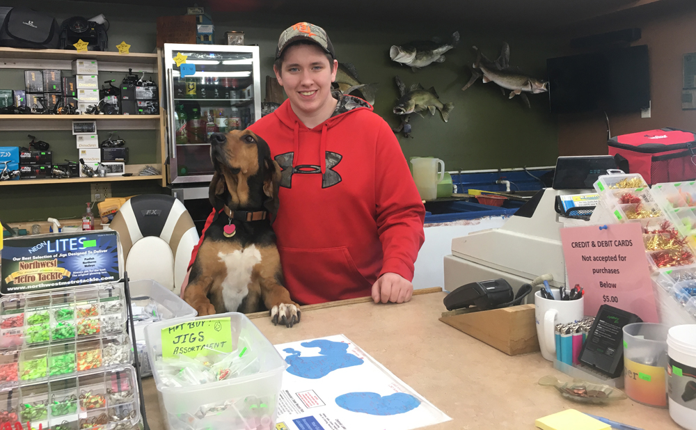 A man stands at the counter in a story with his dog.